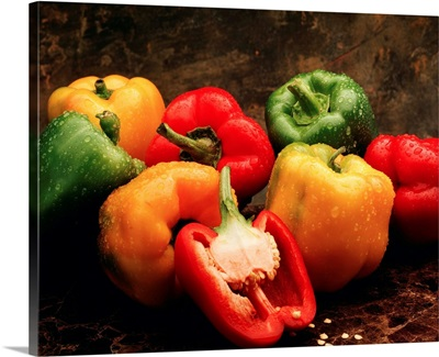 Mixture of green, red and yellow bell peppers, with one red bell pepper cut open