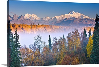 Morning sun lights up Mount McKinley as fog covers the Chulitna River valley, Alaska