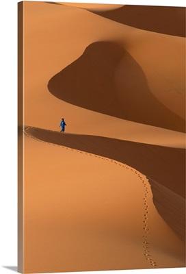 Morocco, Berber 'Blue man' walking across sand dunes in Erg Chebbi area