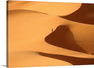 Morocco, Berber 'blue man' walking through sand dunes in Erg Chebbi area, Sahara Deser