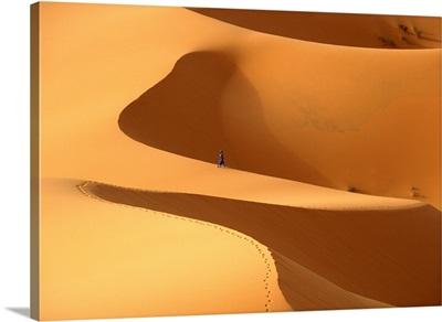 Morocco, Berber 'blue man' walking through sand dunes in Erg Chebbi area, Sahara Desert