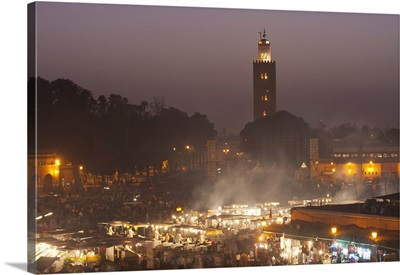 Morocco, food stalls in Dejmaa el Fna at dusk with minaret of Koutoubia mosque