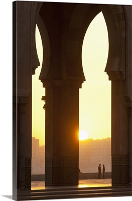 Morocco, Looking through arches of Hassan II mosque to couple chatting, Casablanca