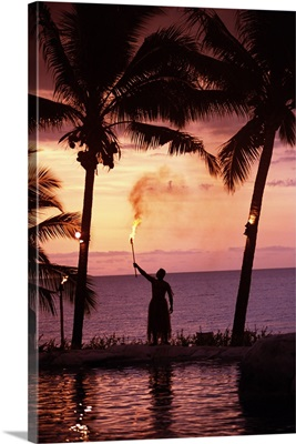 Native In A Grass Skirt Holding A Flaming Torch By Coast At Sunset