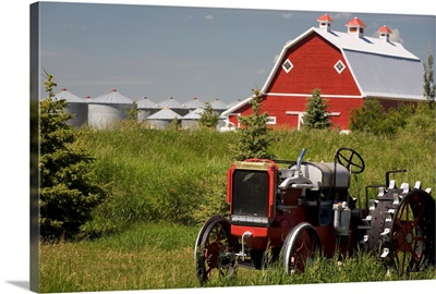 Old Red Tractor In A Field With A Red Barn In The Background, Alberta, Canada
