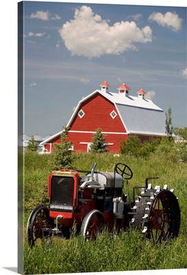 Old Red Tractor In A Field With A Red Barn In The Background; Alberta, Canada