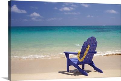 Plumeria Lei Hanging Over Blue Beach Chair Along Shoreline