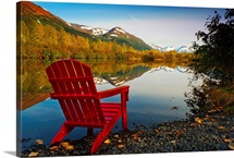 Red Adirondak chair along lakeshore, Alaska