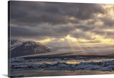 Shafts of sunlight shine on the ice calves in glacial lagoon Jokulsarlon, Iceland
