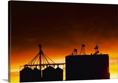 Silhouette of the upper section of a grain elevator at sunset