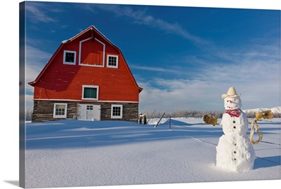 Snowman dressed up as a cowboy standing in front of a vintage red barn
