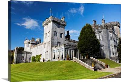 Stone castle on manicured grassy hillside with blue sky and clouds, Ireland