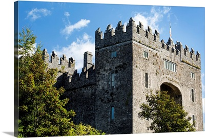 Stone castle with trees, blue sky and clouds, Bunratty, County Clare, Ireland