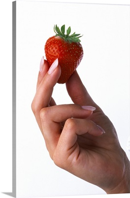 Strawberry being held by a woman's hand