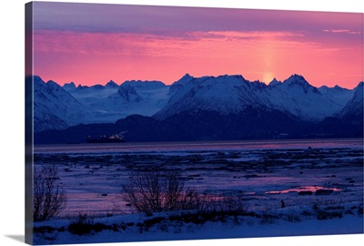 Sun sets over rugged mountain landscape