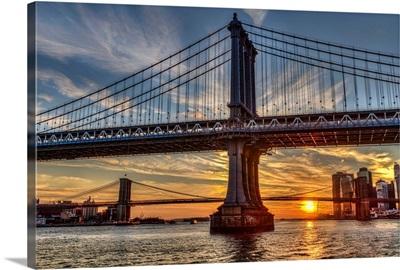 Sun setting behind Manhattan and Brooklyn Bridges; New York City