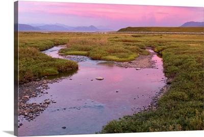 Sunset light reflecting in Sagavanirktok River with trans Alaska Pipeline