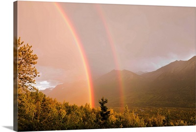 Sunset view of a double rainbow arching over Eagle River Valley after a passing storm, Southcentral Alaska, Summer