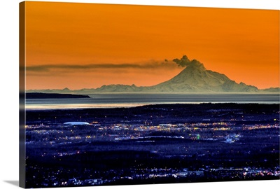 The city of Anchorage Alaska at sunset with Mount Redoubt erupting in the background