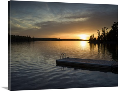 The sun setting over a tranquil lake and silhouetted trees with a dock in the foreground