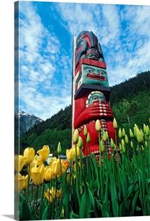 Totem pole with tulips Juneau Southeast Alaska mountains coast summer tourist