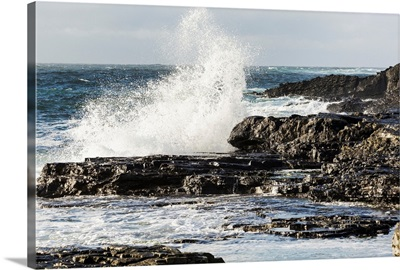 Wave crashing into rocky coast with cloudy sky, Kilkee, County Clare, Ireland