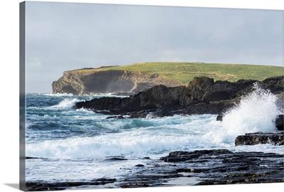 Waves crashing into rocky coast with large grassy hill and cliffs, Kilkee, Ireland