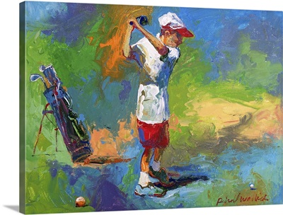 A young boy swinging at the golf ball
