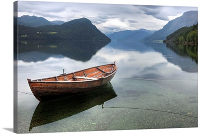 Red rowing boat on a still lake, Norway