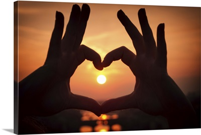 Sunset viewed through fingers forming heart