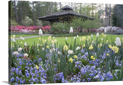 A covered pavilion in a garden of spring flowers