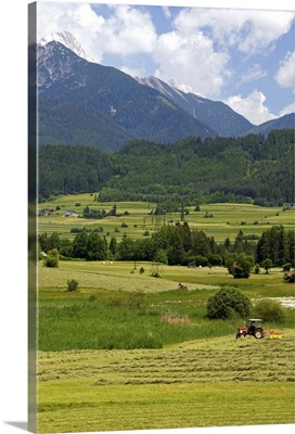 A tractor harvesting a hay field on a farm at Imst, Austria
