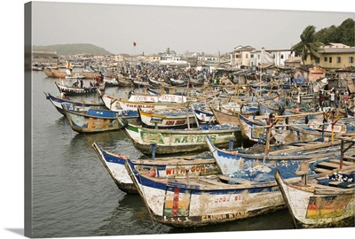 Africa, Ghana, Elmina. Colorful hand-painted fishing boats tied up at Elmina port