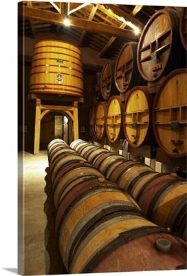 Aging cellar with oak barrels and larger wooden vats, Chateau de Beaucastel, France