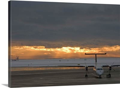 Canada, British Columbia, Vancouver, Dash 8 aircraft with sun lighting distant clouds