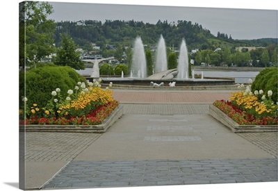 Canada, Quebec, Ville de Saguenay, Chicoutimi. Flowers and fountain