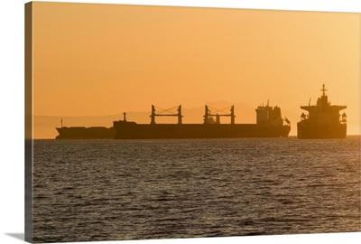 Cargo ship silhouettes in English Bay Beach, Vancouver, Canada
