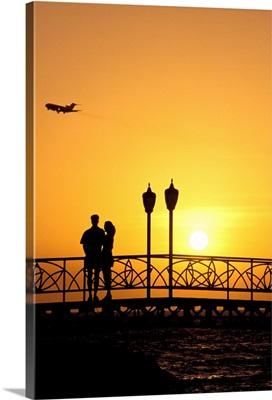 Caribbean, Aruba, Oranjestad, couple on bridge enjoying sunset