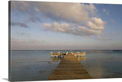 Cayman Islands, Little Cayman Island, Setting sun lights wooden boat pier
