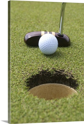 Close-up of putter and gold ball