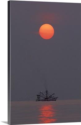 Georgia, Tybee Island. A shrimp boat trawling for shrimp at sunrise
