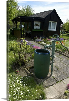 Germany, Straubing, water barrel and pump in cottage garden in Spring