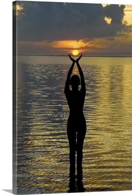 Indonesia, Bali. Woman silhouetted at sunrise on Sanur Beach