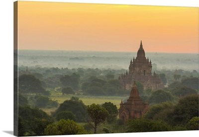 Myanmar. Bagan. Smoke from cooking fires shrouds the temples of Bagan at sunrise