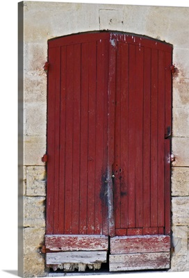 Old red wooden door on one of the winery buildings Chateau Kirwan, Bordeaux, France