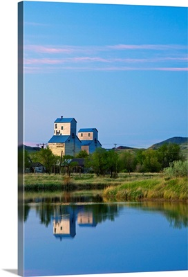 Pair of grain elevators reflect into pond at Sentinel Butte North Dakota