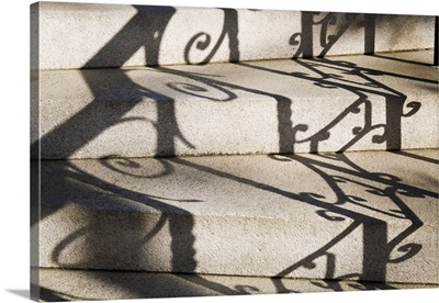 Shadows of wrought iron railing on steps of historic building