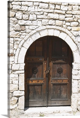 Stone wall with old wooden door with chain and pad lock, Albania, Balkan