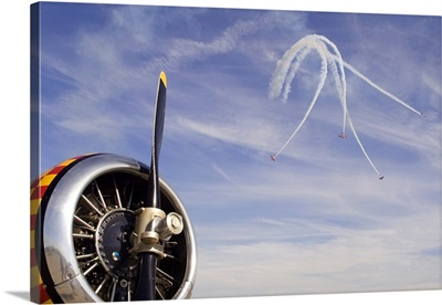 Stunt planes in action at air show with vintage aircraft in the foreground