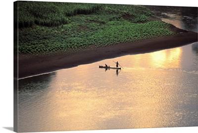 The sun sets on Karo men piloting a dugout raft across the Omo River, Ethiopia, Africa
